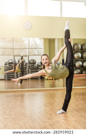 Young slim woman doing standing split at gymnastics training in fitness class - stock photo