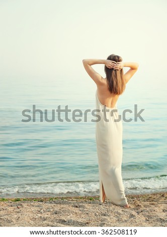 Young slim woman dressed in long white dress with open back, standing back with hands behind head, relaxed breathing ocean fresh air. - stock photo