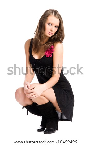 Young slim woman in elegant sitting pose. Isolated on white. - stock photo
