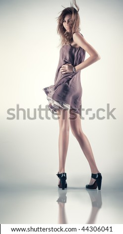 Young slim woman in fluttering dress. - stock photo