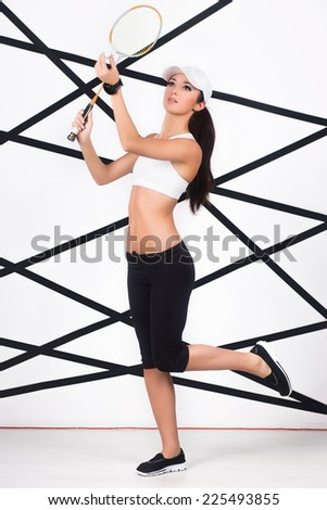 Young slim woman in sportswear playing badminton - stock photo
