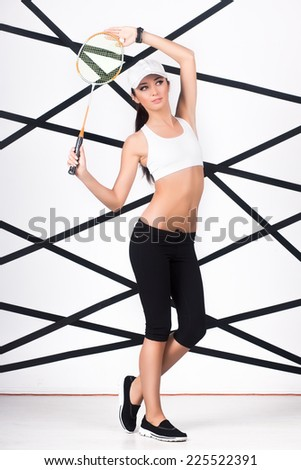 Young slim woman in sportswear posing with badminton racket - stock photo