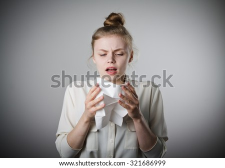Young slim woman is sneezing. - stock photo