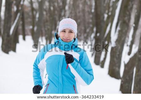Young slim woman jogging in winter park. Running caucasian girl in sportswear - stock photo