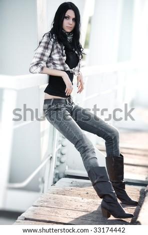 Young slim woman on a bridge. - stock photo
