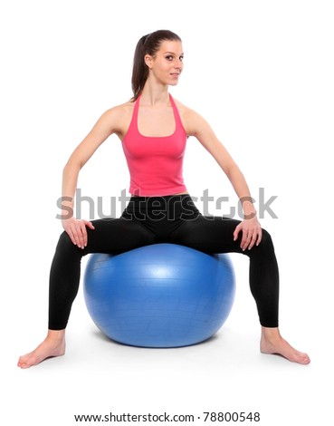 Young slim woman practicing with blue ball on a white background