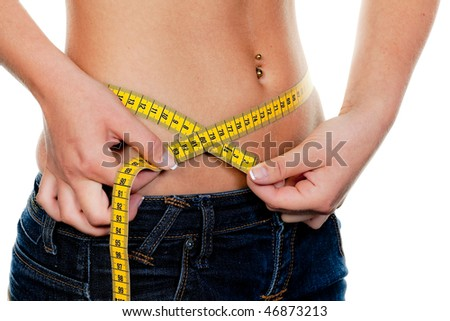 Young, slim woman with measuring tape measure their figure: - stock photo