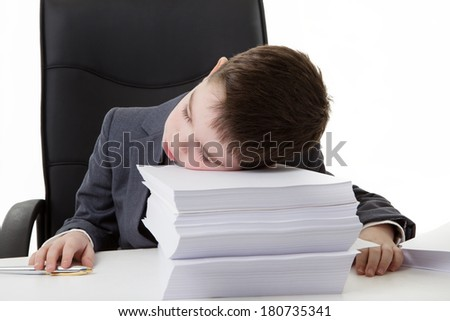 young small boy pretending he's working in an office asleep at his desk on a large pile of paper work to do