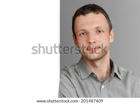 Young smart Caucasian Man, portrait with white wall - stock photo