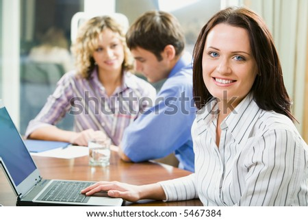 Young smart smiling woman sitting at the table and typing on her laptop