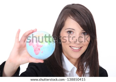 Young smart woman holding the world in her hand - stock photo