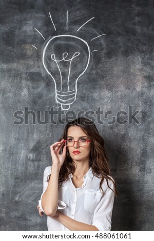 young smart woman in eyeglasses near blackboard with idea symbol lamp