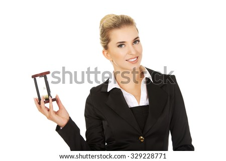 Young smile businesswoman with hourglass - time concept. - stock photo