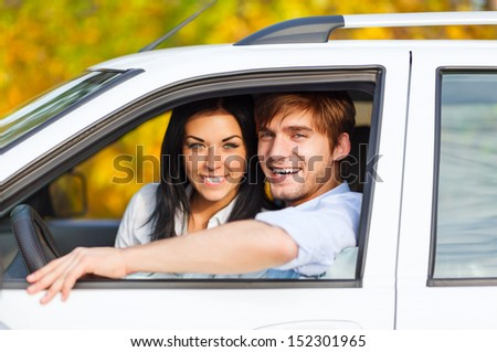 young smile couple driving car, fall season, golden autumn trees, yellow leaves background - stock photo