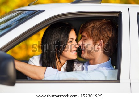 young smile couple romantic kissing sitting in car driving, fall season, golden autumn trees, yellow leaves background