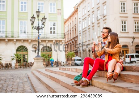 Young smile  couple sitting on stairs in summer , photographs selfie on tablet pc - stock photo