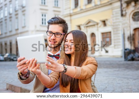 Young smile  couple sitting on stairs in summer , photographs selfie on tablet pc, focus on faces