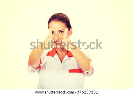 Young smile female doctor or nurse with thumbs up