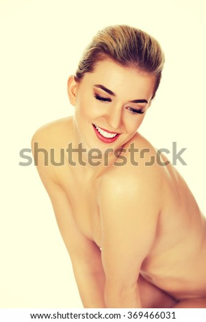 Young smile naked woman sitting on the floor.