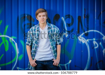 Young smile teenager in front of blue graffiti