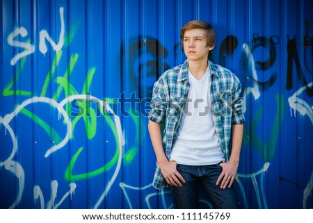 Young smile teenager in front of blue graffiti - stock photo