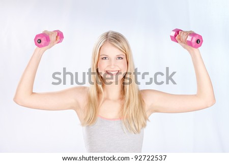 Young smiled woman doing fitness exercises - stock photo