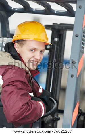 young smiley warehouse worker driver in uniform driving forklift stacker - stock photo