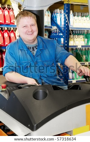 young smiley warehouse worker man driving forklift stacker loader truck in product depot