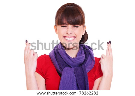 young smiley woman hoping hard with fingers crossed against white background - stock photo