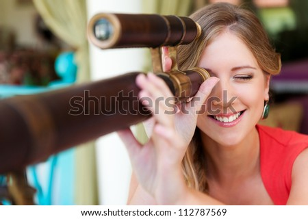 young smiley woman looking through the telescope and smiling - stock photo