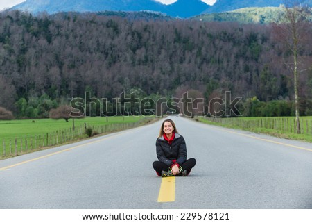 Young smiley woman sitting on an empty road. - stock photo