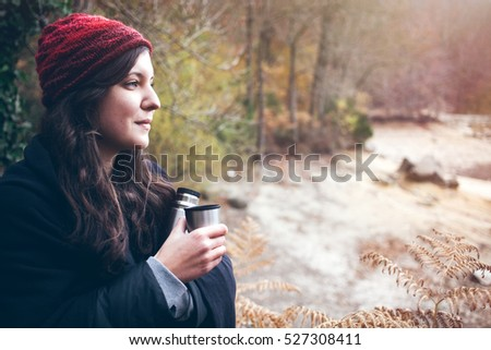 Young smiley woman traveler holding thermos bottle and cup of tea, drinking hot drink while walking in forest. Adventure, travel, tourism and camping concept. Copy space blank for your text
