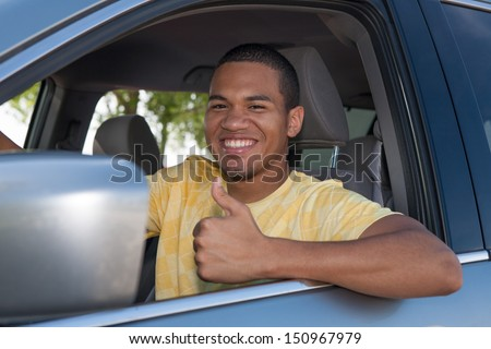 Young Smiling African American Male Thumb up in a Car - stock photo
