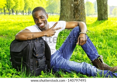 Young smiling african american man with rucksack in a park - stock photo