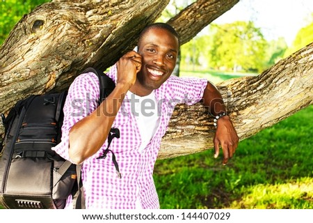 Young smiling african american man with rucksack in a park talking over mobile phone - stock photo