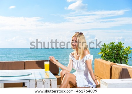 Young smiling and happy woman drinking juice in beach cafe with sky and sea background.