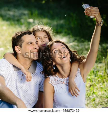 Young smiling and laughting happy family of three taking selfie in the park - stock photo