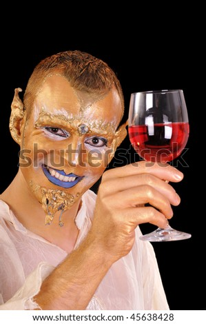 Young smiling artistic painted man with glass of beverage - stock photo