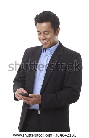 Young smiling Asian businessman dialing on mobilephone. - stock photo