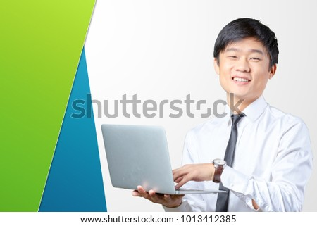 young smiling asian businessman holding laptop