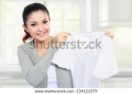 young smiling asian woman showing white clean clothes - stock photo