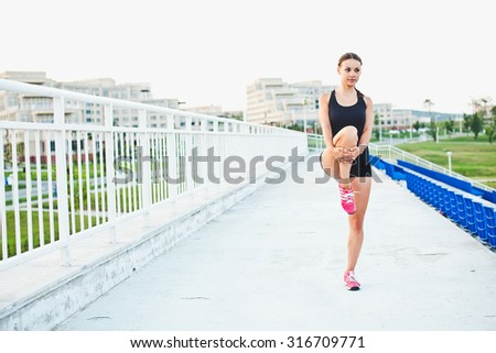 Young smiling attractive sporty girl runner holds her leg while stretching outdoors at stadium of her university campus - stock photo