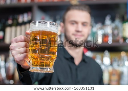 Young smiling bartender with beer on the bar - stock photo
