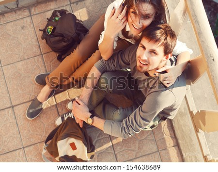 Young smiling beautiful couple sitting on the ground in summer having fun outdoor.  - stock photo