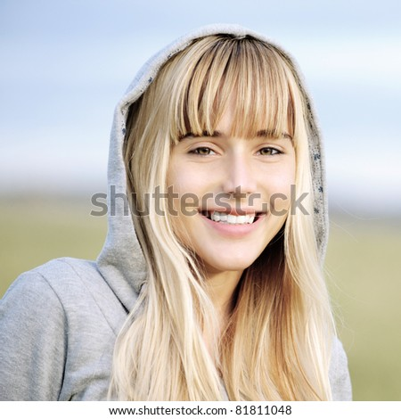 Young smiling beautiful girl in jacket with hood against autumn nature. - stock photo