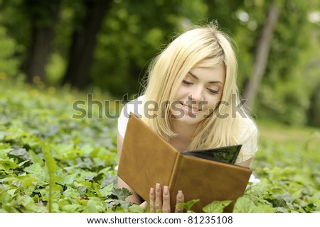 Young smiling beautiful girl reading a book outdoor.