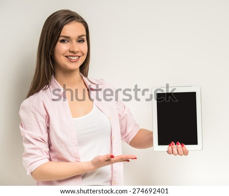 Young smiling beautiful girl standing on grey background and showing a blank digital tabet screen. - stock photo