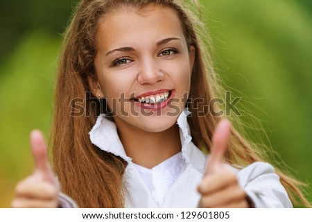 Young smiling beautiful woman lifts thumbs upwards, against background of autumn park. - stock photo
