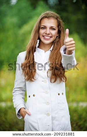 Young smiling beautiful woman lifts thumbs upwards, against background of autumn park.