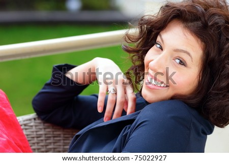 Young smiling beautiful woman sitting in the garden with green grass in the background